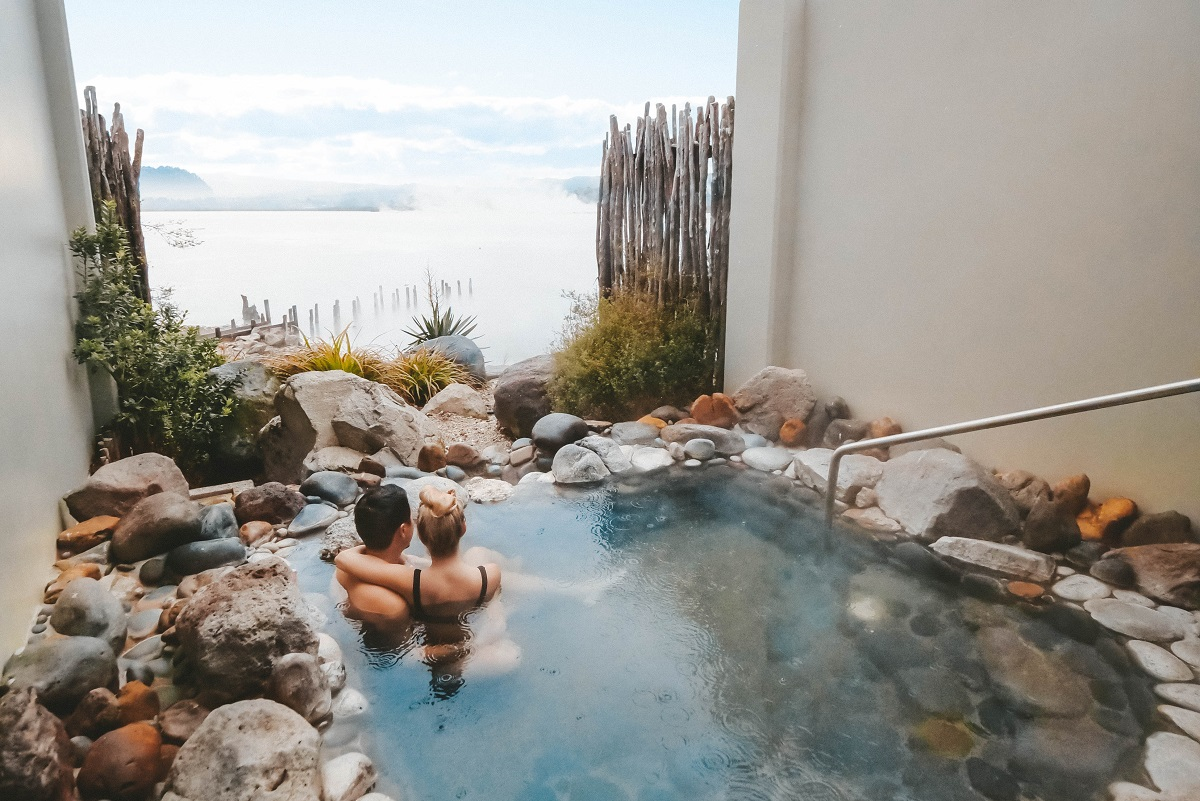 Couple enjoying the view from a natural hot pool in Rotorua, New Zealand