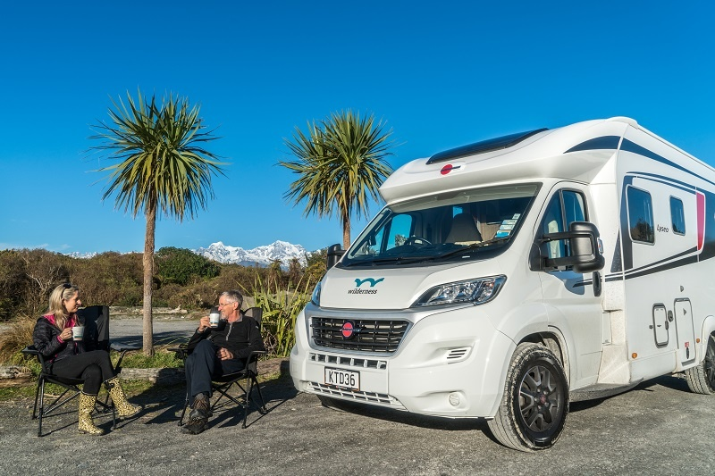 Dad and daughter having coffee next to their Wilderness Motorhome at Gillespies Beach NZ