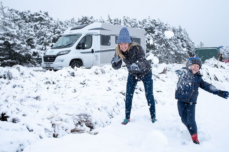 Family playing in the snow during their NZ campervan holiday