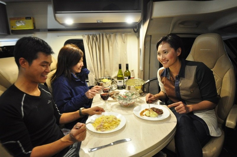 Friends enjoying a dinner in their motorhome rental