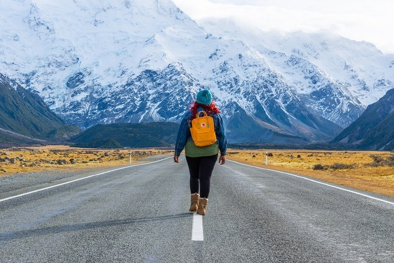 Girl walking on a road in Mount Cook National Park New Zealand