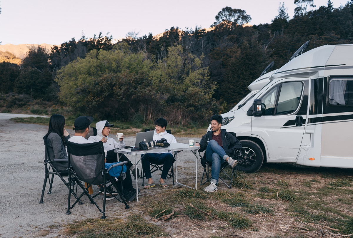 Group of friends relaxing outside their campervan in NZ