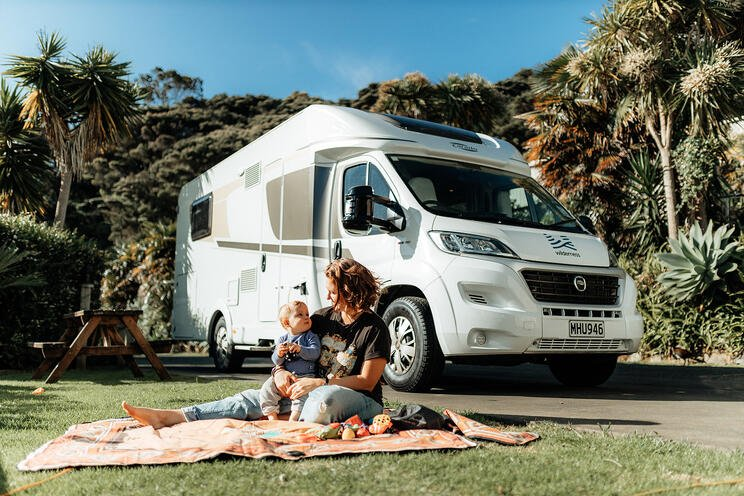 baby and mum on picnic mat on grass by motorhome