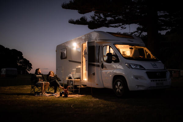 mum and dad outside motorhome on camping chairs while baby naps