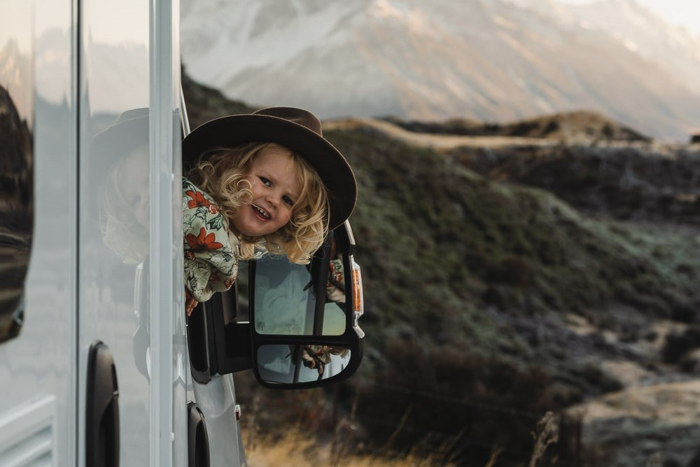 toddler leaning out motorhome window mountains child toddler compact plus wilderness motorhome new zealand
