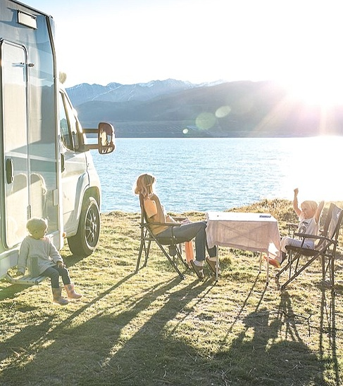 family sitting next to their motorhome on the water