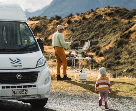 family barbeque outside wilderness motorhome 552 x 451px