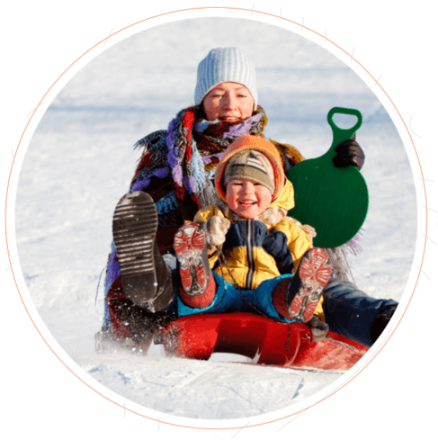 Mother and child on a sled in the snow